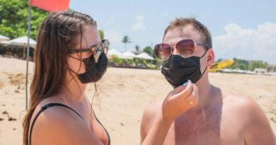 un homme et une femme portent des masque de protection noirs à la plage